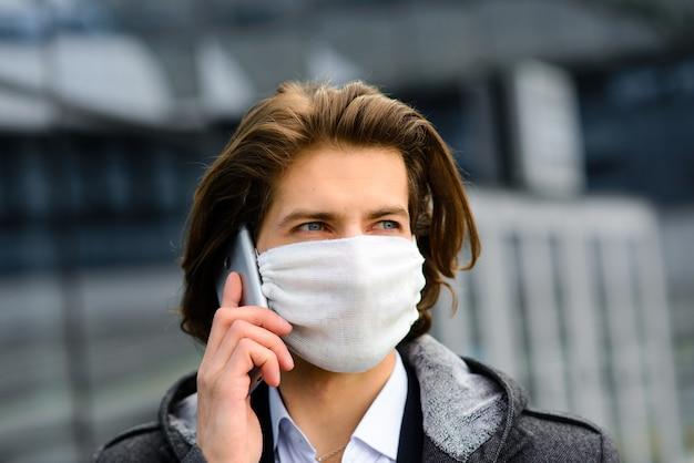 Młody człowiek w medycznej masce na zewnątrz, bez pieniędzy, kryzysu, ubóstwa, trudów. kwarantanna, koronawirus, izolacja.