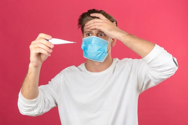 Młody człowiek w medycznej masce ochronnej patrząc na cyfrowy termometr w panice zszokowany i zaskoczony na białym tle różowym