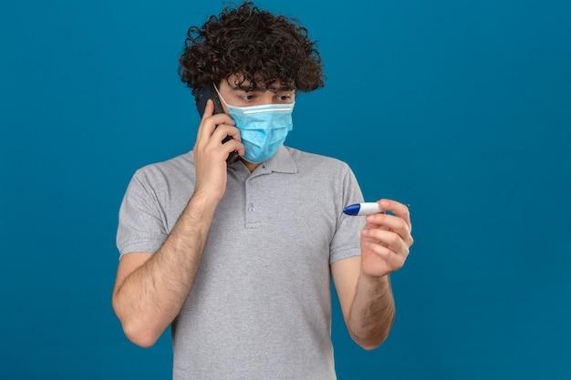Młody człowiek w medycznej masce ochronnej patrząc na cyfrowy termometr w ręku, nerwowo patrząc na na białym tle niebieskim tle