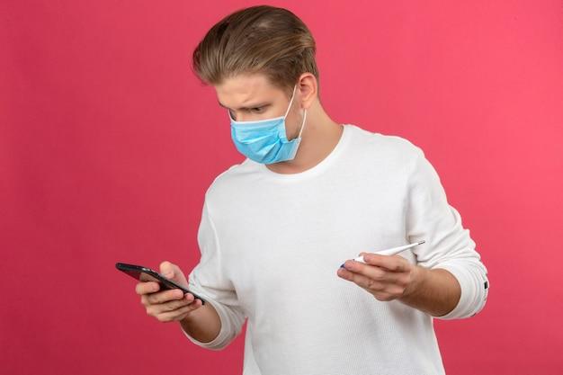 Młody człowiek w medycznej masce ochronnej patrząc na ekran smartfona w panice i trzymając w drugiej ręce cyfrowy termometr na na białym tle różowym tle