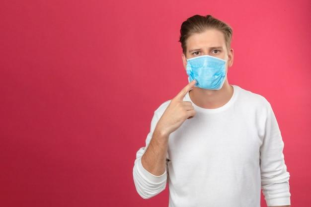 Młody człowiek w medycznej masce ochronnej patrząc na kamerę, wskazując palcem na maskę medyczną, musisz nosić maskę, aby uniknąć zachorowania na izolowanym różowym tle