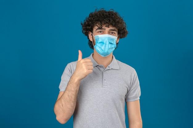 Młody człowiek w medycznej masce ochronnej patrząc na kamery z radosną twarzą pokazując kciuk do góry na odosobnionym niebieskim tle