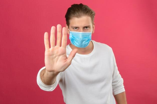 Młody człowiek w medycznej masce ochronnej robi znak stopu ręką patrząc na kamery z poważną twarzą stojącą na na białym tle różowym tle