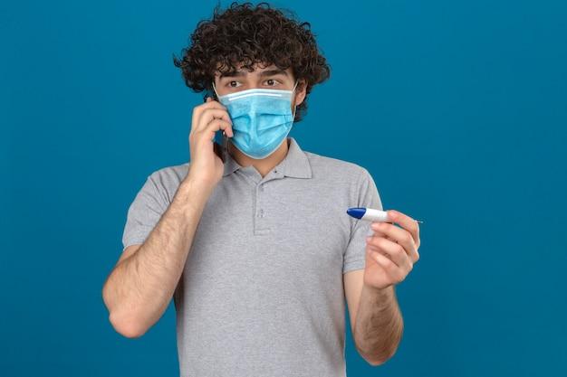 Młody człowiek w medycznej masce ochronnej rozmawia przez telefon komórkowy trzymając w drugiej ręce cyfrowy termometr, patrząc nerwowo na odosobnionym niebieskim tle