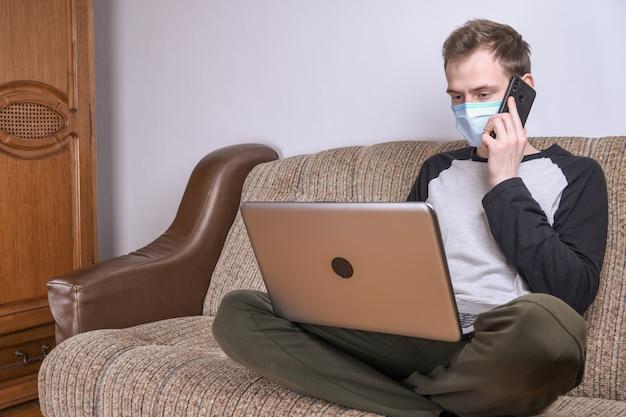 Młody człowiek w medycznej masce pracuje w domu w pokoju na kanapie używać laptop. kwarantanna, samoizolacja, ochrona przed koronawirusem. wakacje z pracy.