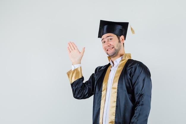 Młody człowiek w mundurze absolwenta macha ręką na powitanie i wesoło, widok z przodu.