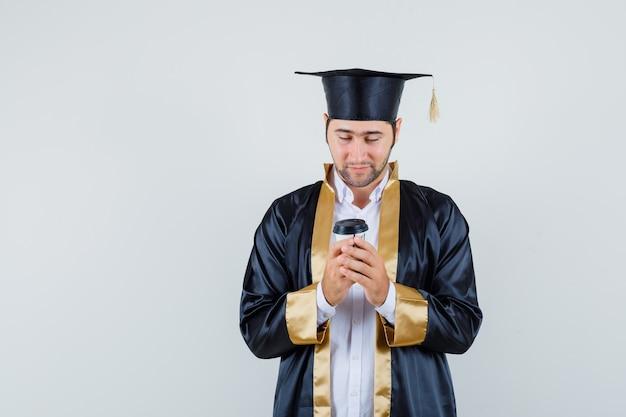Młody człowiek w mundurze absolwenta patrząc na papierowy kubek do kawy, widok z przodu.