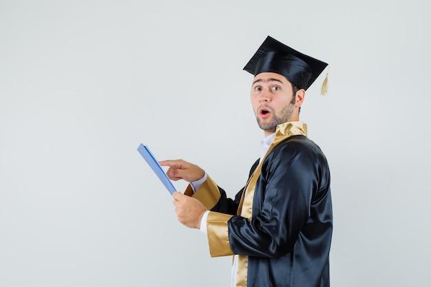 Młody Człowiek W Mundurze Absolwenta Przeglądający Notatki W Schowku I Patrząc Zdziwiony. Darmowe Zdjęcia