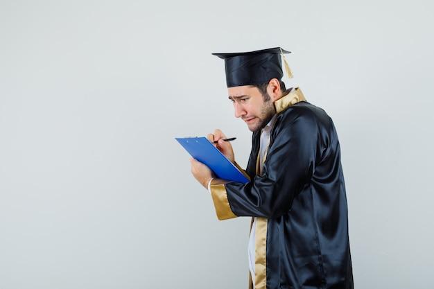 Młody Człowiek W Mundurze Absolwenta Robienia Notatek W Schowku I Smutny Patrząc. Darmowe Zdjęcia