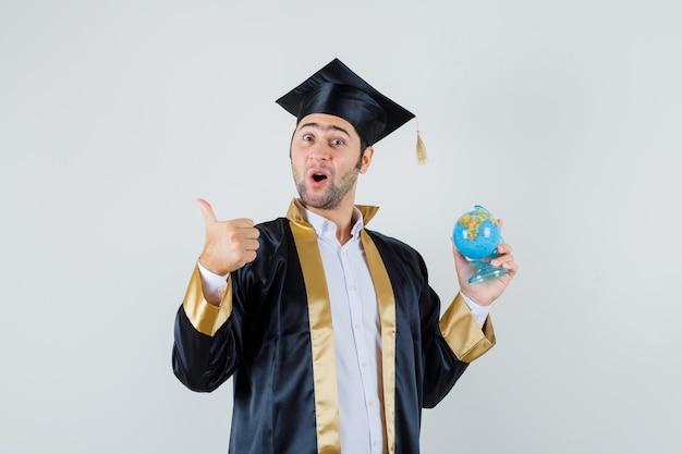 Młody człowiek w mundurze absolwenta trzymając kulę ziemską szkoły, pokazując kciuk do góry i patrząc wesoło, widok z przodu.