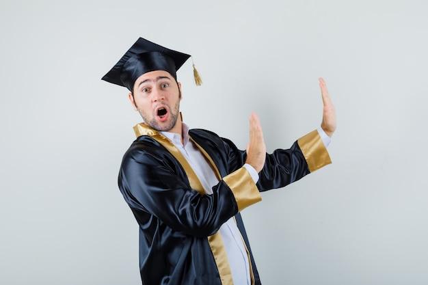 Młody człowiek w mundurze absolwenta, trzymając się za ręce, aby się bronić i patrząc przestraszony, widok z przodu.