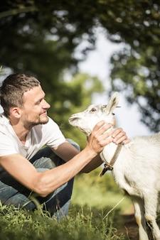 Młody człowiek w naturze z kozą