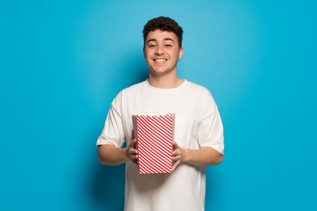 Młody człowiek w niebieska ściana jedzenia popcorns