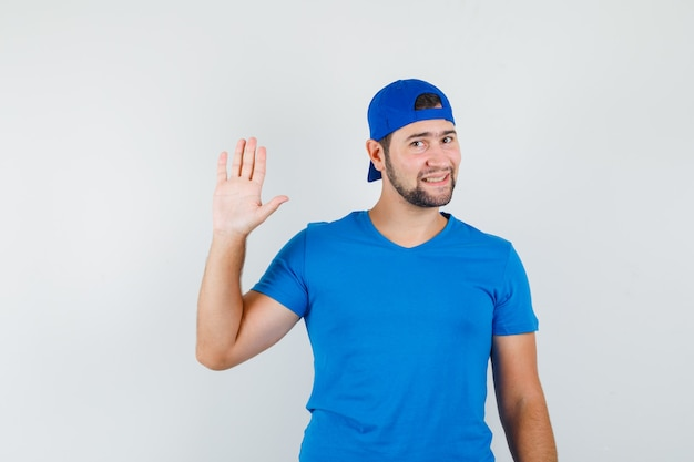 Młody człowiek w niebieskiej koszulce i czapce, machający ręką, by się pożegnać i wyglądający wesoło