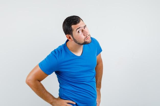 Młody człowiek w niebieskiej koszulce i czapce pochyla głowę, by wyraźnie usłyszeć i wyglądać zaciekawiony