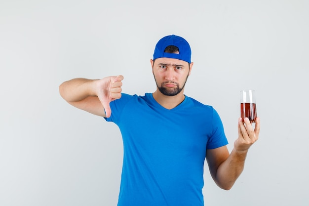 Młody człowiek w niebieskiej koszulce i czapce trzyma zimny napój z kciukiem w dół i wygląda na rozczarowanego