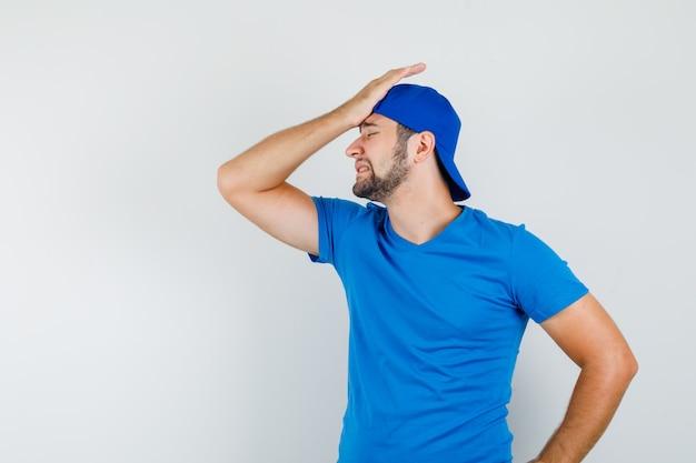 Młody człowiek w niebieskiej koszulce i czapce, trzymając rękę na głowie i patrząc przepraszam