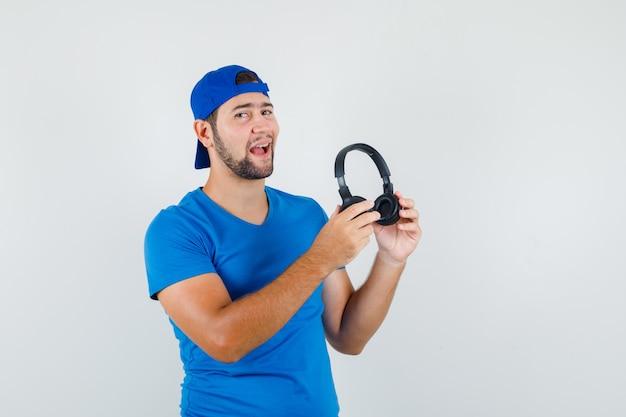 Młody człowiek w niebieskiej koszulce i czapce, trzymając słuchawki i patrząc optymistycznie