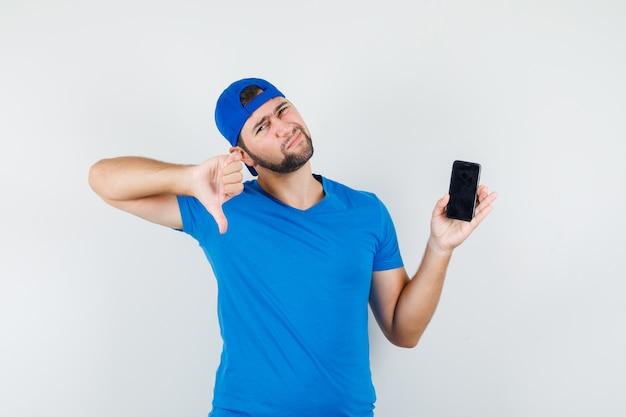Młody człowiek w niebieskiej koszulce i czapce, trzymając telefon komórkowy z kciukiem w dół i patrząc niezadowolony