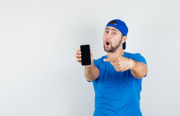 Młody człowiek w niebieskiej koszulce i czapce, wskazując na telefon komórkowy