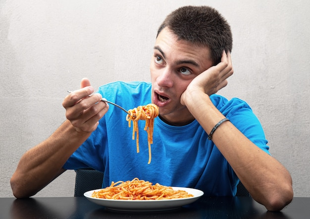 Młody człowiek w niebieskiej koszulce je spaghetti