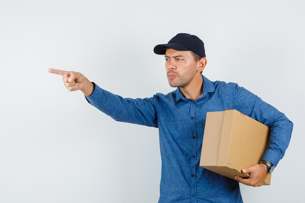 Młody człowiek w niebieskiej koszuli, czapka trzymając karton, wskazując od przodu, widok z przodu.