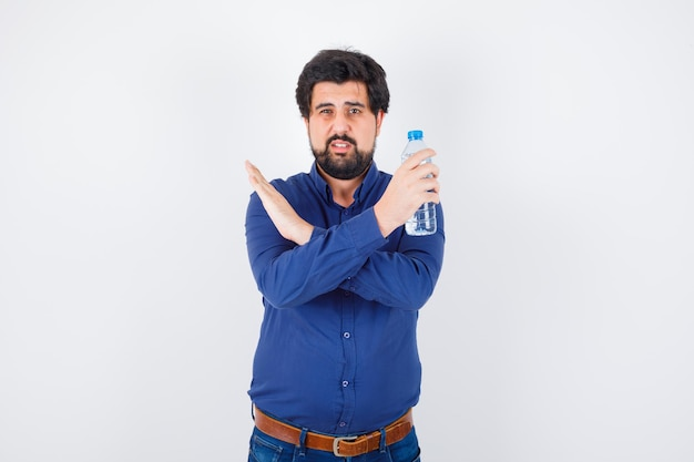 Młody człowiek w niebieskiej koszuli i dżinsach, trzymając butelkę wody i pokazując gest x i patrząc poważnie, widok z przodu.