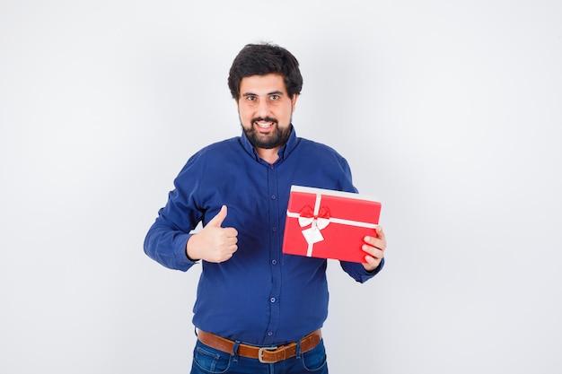 Młody człowiek w niebieskiej koszuli i dżinsach, trzymając pudełko i pokazując kciuk w górę i patrząc optymistycznie, widok z przodu.