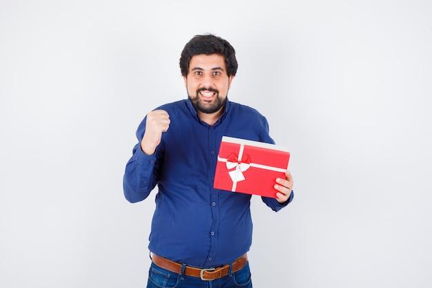 Młody człowiek w niebieskiej koszuli i dżinsach, trzymając pudełko i zaciskając pięść i patrząc szczęśliwy, widok z przodu.