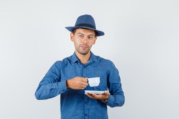 Młody człowiek w niebieskiej koszuli, kapelusz pije kawę po turecku i wygląda pozytywnie, widok z przodu.