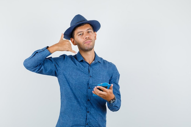 Młody człowiek w niebieskiej koszuli, kapelusz trzymając schowek z gestem telefonu i patrząc pomocny, widok z przodu.