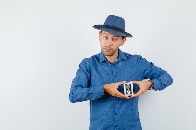 Młody człowiek w niebieskiej koszuli, kapeluszu trzymając klepsydrę i patrząc rozsądnie, widok z przodu.