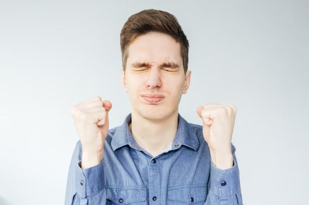 Młody człowiek w niebieskiej koszuli na jasnoszarym tle. mężczyzna zaciska pięści w gniewie