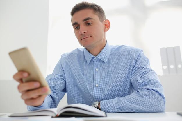 Młody człowiek w niebieskiej koszuli patrzy na ekran smartfona, siedząc przy biurku