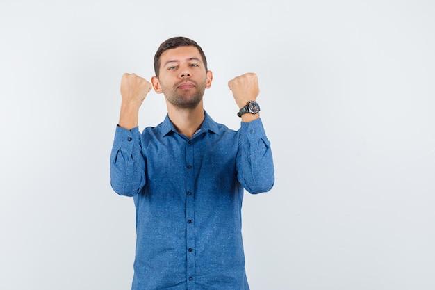 Młody człowiek w niebieskiej koszuli podnosi zaciśnięte pięści i wygląda pewnie, widok z przodu.