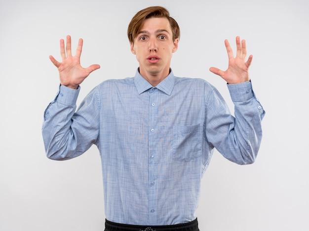 Młody człowiek w niebieskiej koszuli podnosząc ręce w kapitulacji, przestraszony, jest zdezorientowany stojąc nad białą ścianą