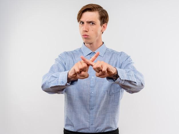 Młody człowiek w niebieskiej koszuli robi gest obrony, krzyżując palce wskazujące z poważną twarzą stojącą nad białą ścianą