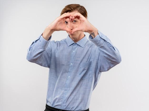 Młody człowiek w niebieskiej koszuli robi herat gest z palcami patrząc na kamery przez palce stojąc na białym tle