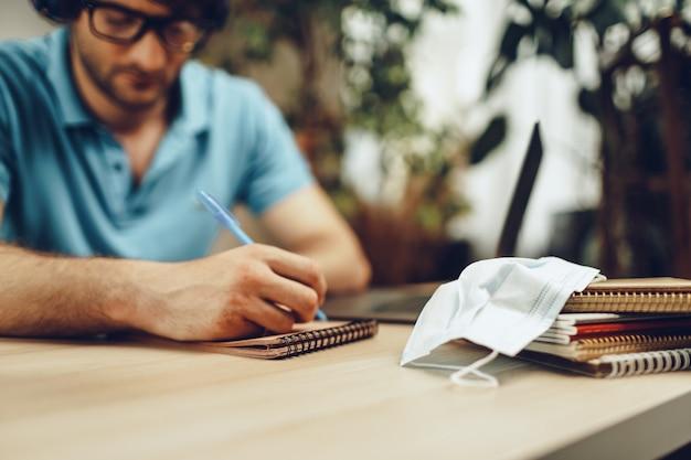 Młody człowiek w niebieskiej koszuli siedzi przy stole i uczy się z laptopem