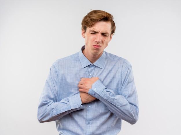 Młody człowiek w niebieskiej koszuli, trzymając hnads na klatce piersiowej, patrząc źle, czując ból stojąc nad białą ścianą
