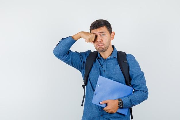 Młody człowiek w niebieskiej koszuli, trzymając schowek, jednocześnie przecierając oko i patrząc smutno, widok z przodu.