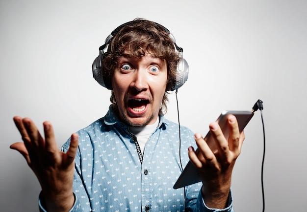 Młody człowiek w niebieskiej koszuli, trzymając tablet i noszenie słuchawek