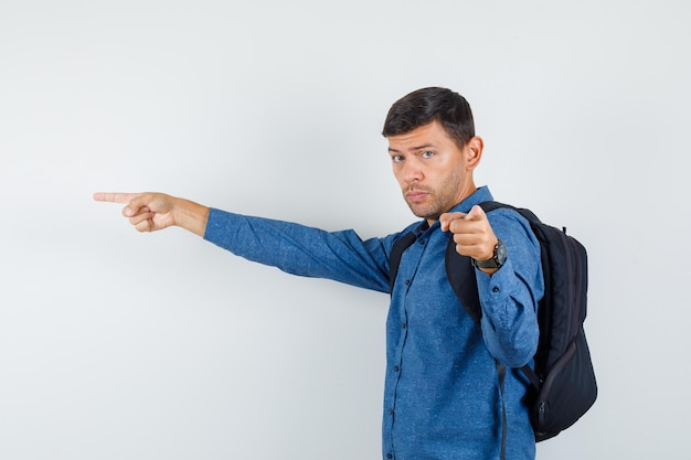 Młody człowiek w niebieskiej koszuli, wskazując na bok i aparat i patrząc poważnie.