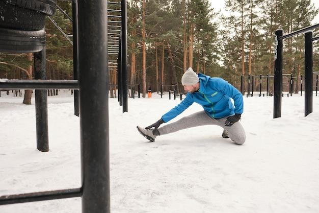 Młody człowiek w niebieskiej kurtce siedzi na jednym kolanie i rozciągając nogę w pozycji kucającej podczas treningu na zimowym obszarze treningowym