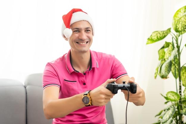 Młody człowiek w nowym roku czerwona czapka, grając w gry wideo z joystickiem w salonie. świąteczna zabawa, sama w domu ciesząc się