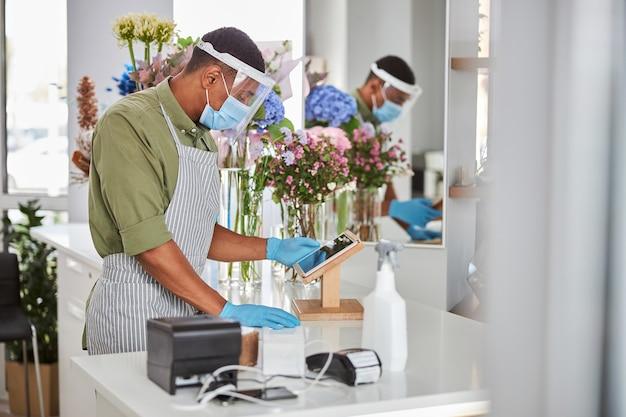 Młody człowiek w ochronie antywirusowej pracuje przy kasie z touchpadem i terminalem pos w kwiaciarni