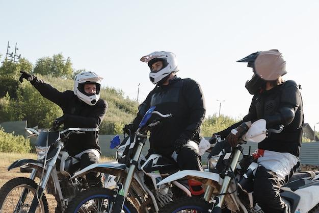 Młody człowiek w odzieży ochronnej i kaskach pokazuje kierunek podczas omawiania trasy motocyklowej z przyjaciółmi