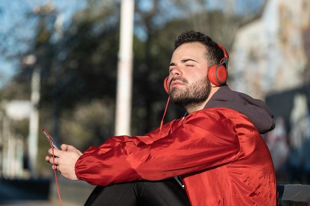 Młody człowiek w odzieży sportowej, słuchanie muzyki z parą słuchawek