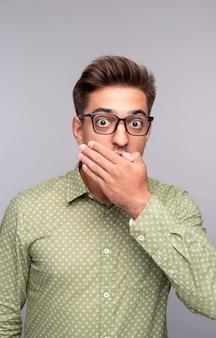 Młody człowiek w okularach i casualowej koszuli zakrywającej usta dłonią i wyglądający na zszokowany podczas otrzymywania niewiarygodnych wiadomości na szarym tle