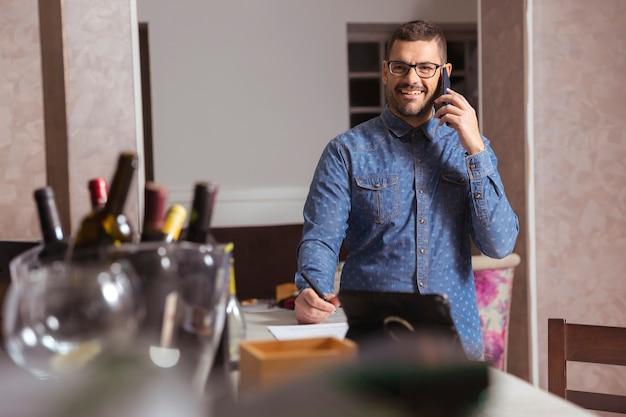 Młody człowiek w okularach i koszuli rozmawia przez telefon w koktajl barze